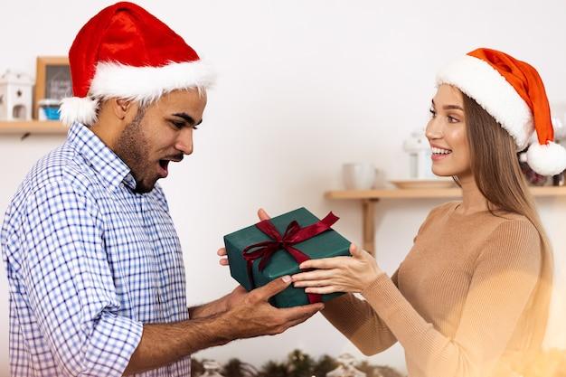Romantica coppia multietnica in cappelli di natale che si scambiano regali, ritratto ravvicinato
