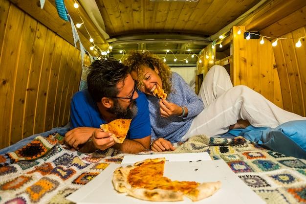 Le persone romantiche adulte giovani coppie innamorate si godono la piccola casa all'interno di un vecchio furgone vintage restaurato mangiando pizza insieme e divertendosi
