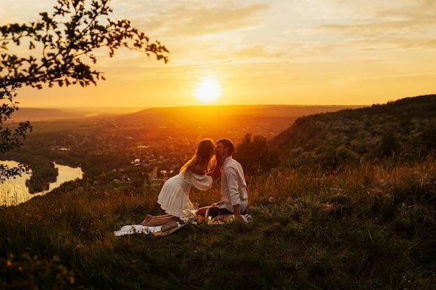 Picnic romantico delle coppie nell'amore sulla montagna al tramonto splendido. si baciano e provano amore.