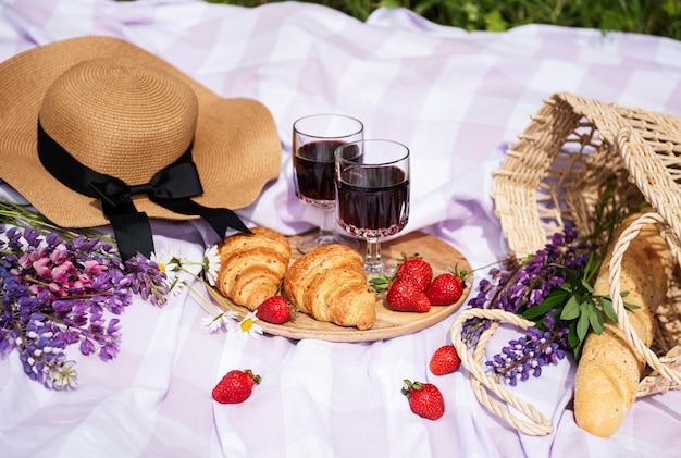 Scena di picnic romantico il giorno d'estate. picnic all'aperto con vino e frutta all'aperto sullo sfondo dell'erba verde.