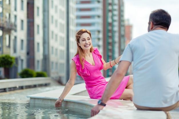 Luogo romantico. donna allegra positiva che si siede vicino alla fontana mentre era ad un appuntamento con il suo fidanzato