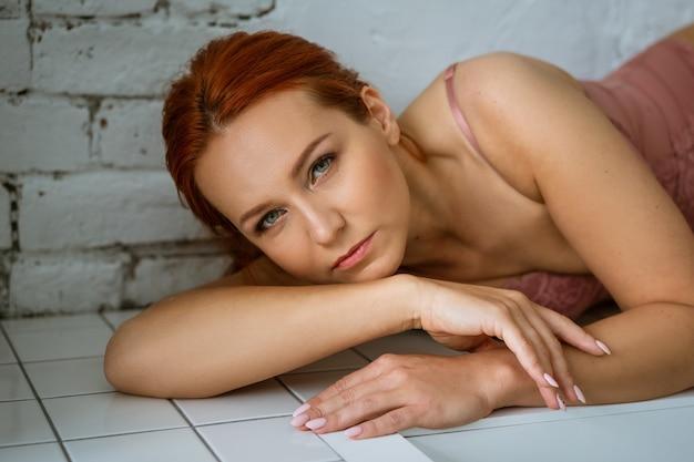 Ritratto romantico di una bella donna rossa in lingerie rosa guarda nel telaio
