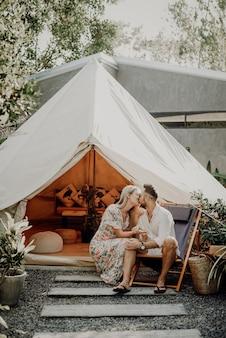 Ritratto romantico di coppia che celebra la luna di miele durante le vacanze e il tour in thailandia. amorevole moglie e marito si baciano sullo sfondo della tenda e della natura in una giornata di sole.