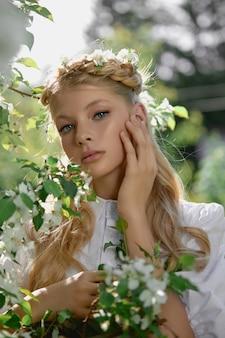 Ritratto romantico di una ragazza nel parco vicino a un melo in fiore. cosmetici naturali. bellezza naturale di una donna in abito bianco