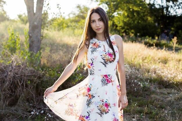 Ritratto romantico di ragazza nel soleggiato giardino estivo