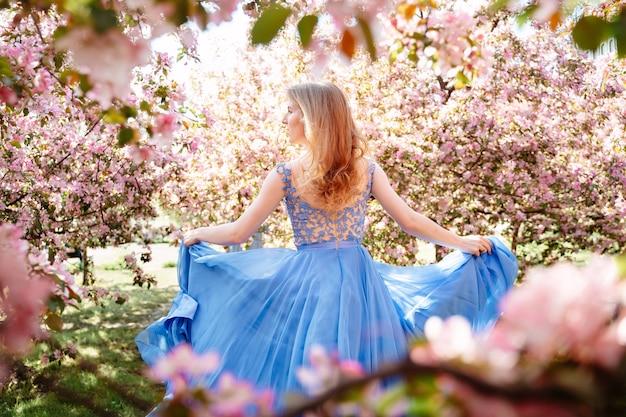 Ritratto romantico di una bella ragazza in fuga in un lungo vestito blu oltremare di rosa sakura nel giardino