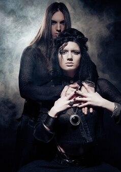 Ritratto romantico di giovane coppia gotica - uomo e donna su sfondo scuro.