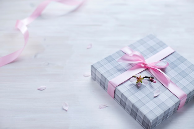 Scatola regalo romantica con nastro rosa su fondo in legno chiaro