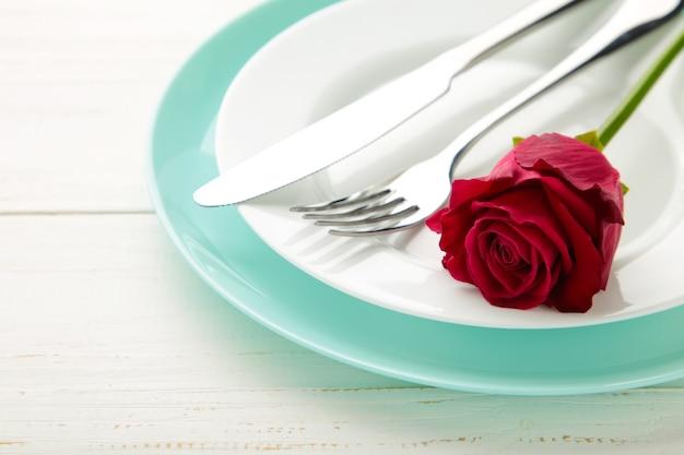 Regolazione della tabella del ristorante romantico con una rosa rossa sui piatti