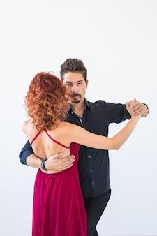 Danza romantica e sociale, concetto della gente - coppia che balla la salsa o il kizomba o il tango su bianco