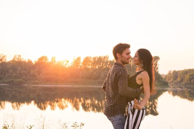 Romantico, ballo sociale e concetto di persone - giovani coppie che ballano bachata sullo sfondo del tramonto