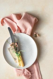 Regolazione della tavola romantica o primaverile coltello e forchetta fiorellini rosa e tovagliolo di lino su un piatto