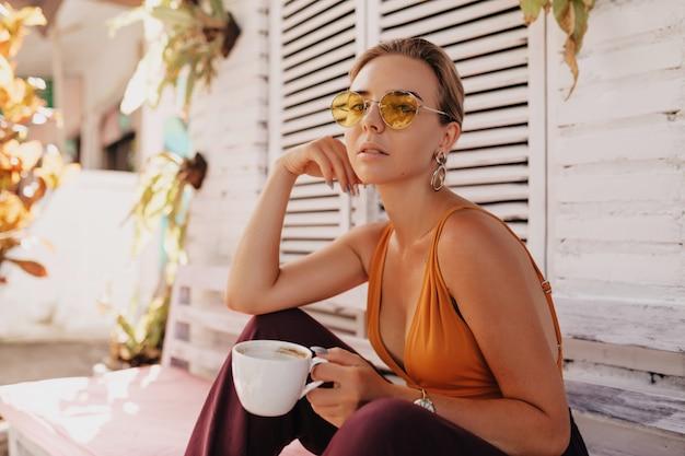 Donna elegante romantica con capelli biondi che indossa occhiali da sole alla moda rotondi e maglietta arancione che si siedono fuori con caffè