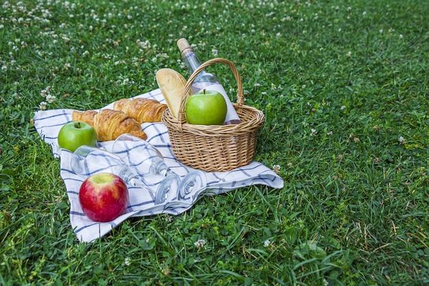 Pranzo al sacco estivo romantico all'aperto. cesto di vimini con croissant, mele e bottiglia di vino rosato su tela a scacchi sull'erba nel parco.