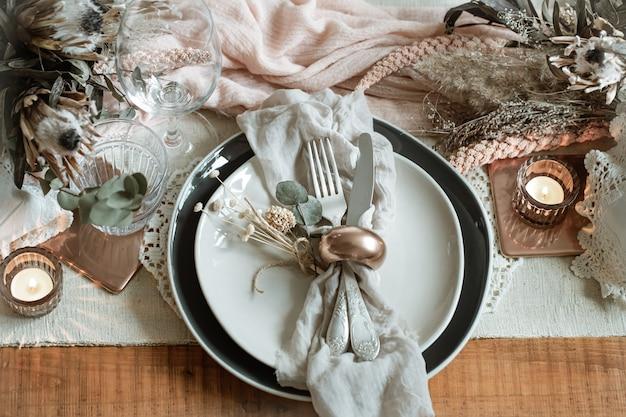 Romantica tavola con candele accese e fiori secchi per il matrimonio con molti dettagli decorativi.