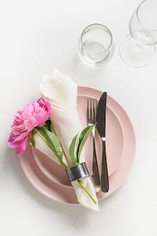 Regolazione romantica della tavola con la peonia rosa per la festa festiva sulla tavola bianca.