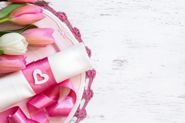 Regolazione romantica della tavola con i fiori del tulipano e la vista superiore del nastro rosa con lo spazio della copia