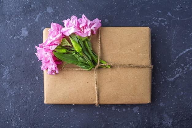 Romantica natura morta vintage con graziosa confezione regalo avvolta con carta artigianale e decorata con fiori rosa su sfondo scuro