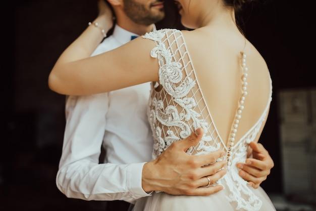 Momento romantico del matrimonio, coppia di sposi che abbraccia.