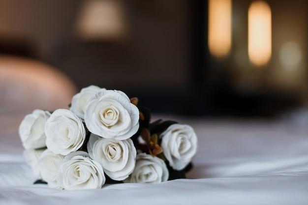 Romantico secchio di fiori di rosa bianca sul letto bianco