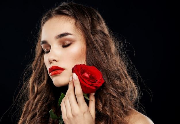 Donna romantica su sfondo nero con fiore rosso nelle sue mani
