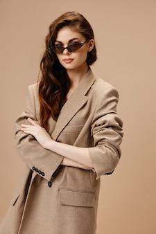 Donna romantica in cappotto e occhiali su uno sfondo beige in attesa