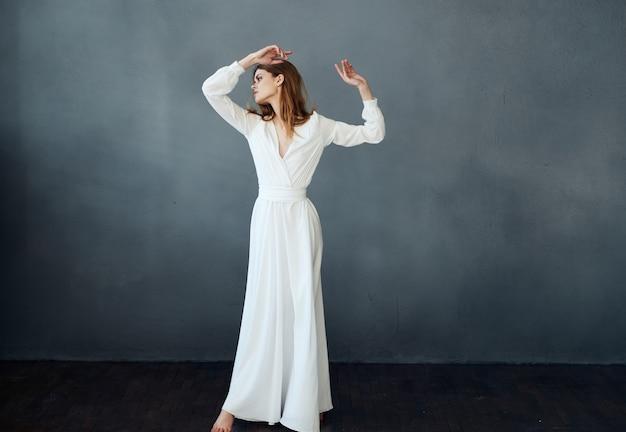 Donna romantica in piena crescita su uno sfondo grigio in un abito bianco copia spazio. foto di alta qualità