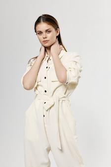 Donna romantica in abiti leggeri tocca il viso con le mani su sfondo isolato.