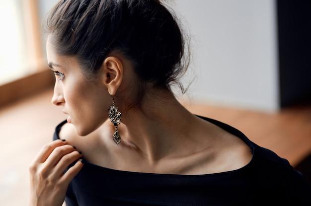 Donna romantica modello ritratto orecchini trucco e abito da sera sfondo chiaro