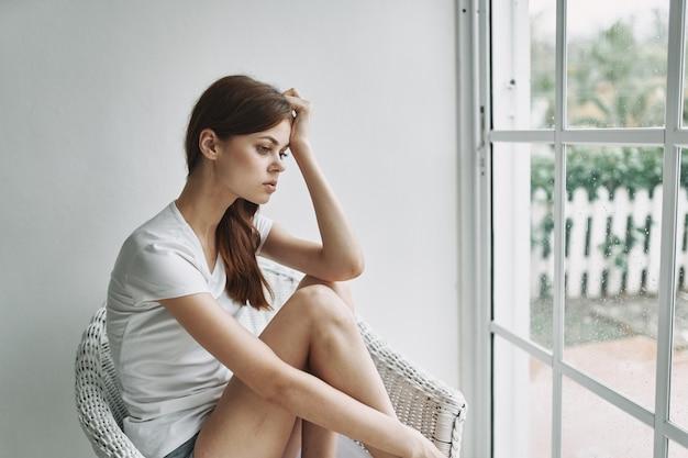 La donna romantica vicino alla finestra si siede su una sedia