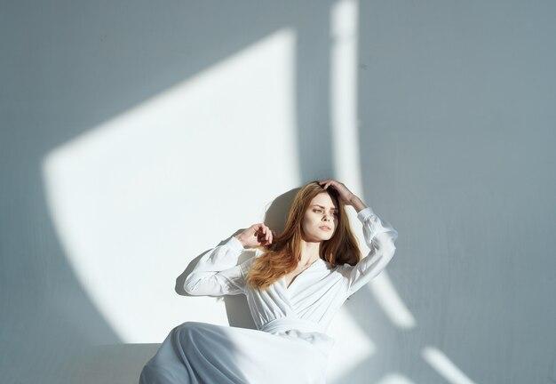 Donna romantica in un prendisole al chiuso e luce che cade sul muro. foto di alta qualità