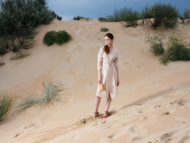 Donna romantica con un pettine in un prendisole bianco e scarpe rosse si trova sulla sabbia