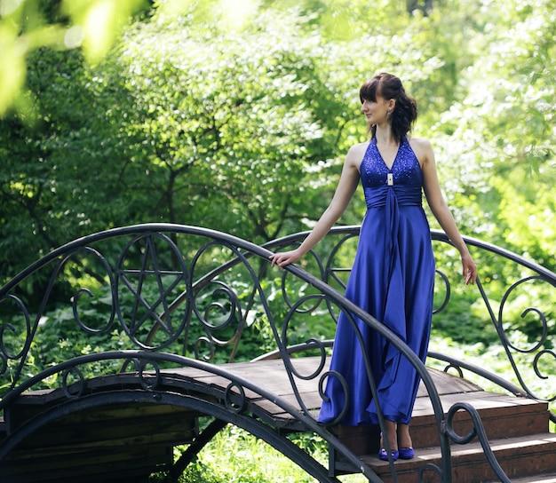 Donna romantica con abito lungo nel parco