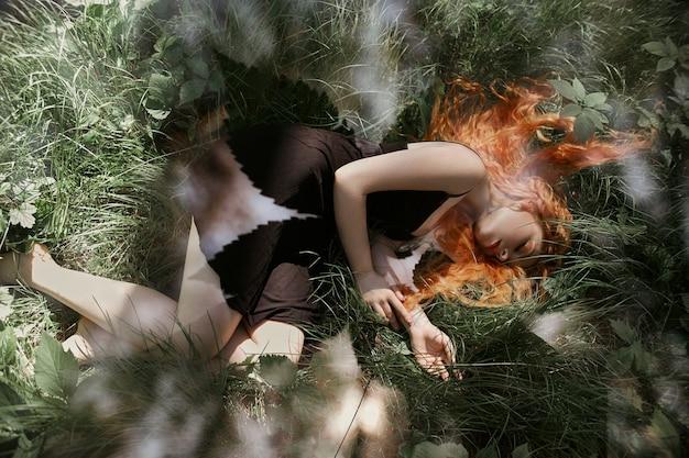 Donna romantica con capelli rossi che si trova nell'erba nel bosco. una ragazza con un vestito nero chiaro dorme e sogna in una foresta magica