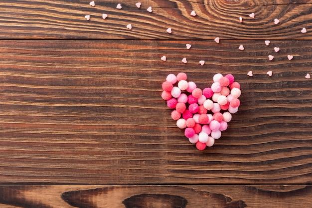 Sfondo romantico in legno per san valentino con soffice cuore di lana e tanti cuoricini