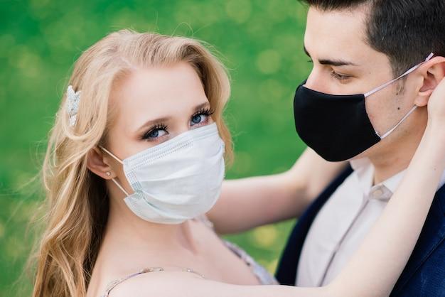 Giovani belle coppie romantiche che godono del tempo insieme indossando maschere protettive