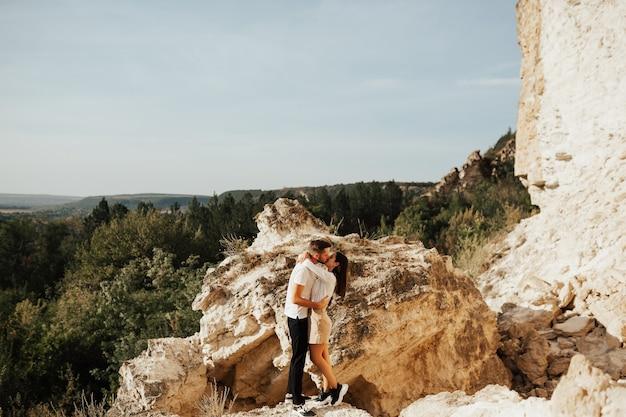 Giovani coppie romantiche che baciano appassionatamente sulle montagne della pineta.