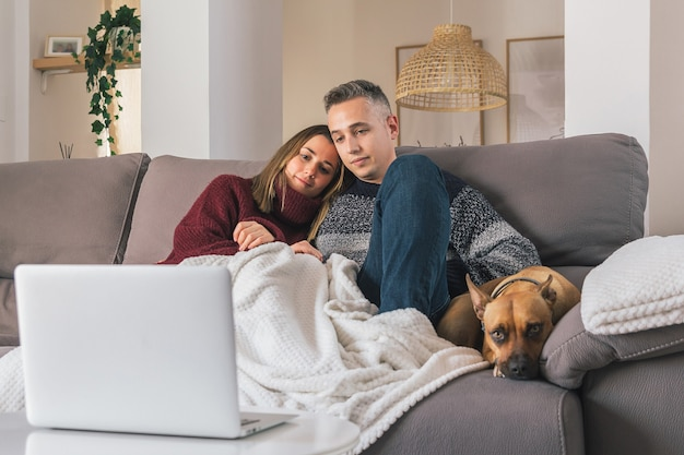 Giovani coppie romantiche e il loro cane a casa accogliente, rilassarsi sul divano mentre si guardano film sul laptop