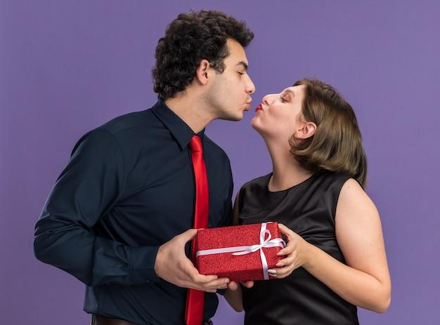 Romantica giovane coppia il giorno di san valentino uomo che dà un pacchetto regalo alla donna che si guardano l'un l'altro baciandosi isolato sul muro viola