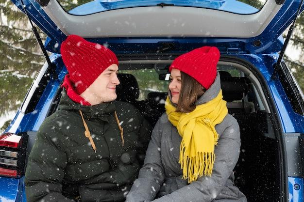 Coppie romantiche giovani hipster che abbracciano mentre era seduto nel bagagliaio della macchina sotto la neve che cade