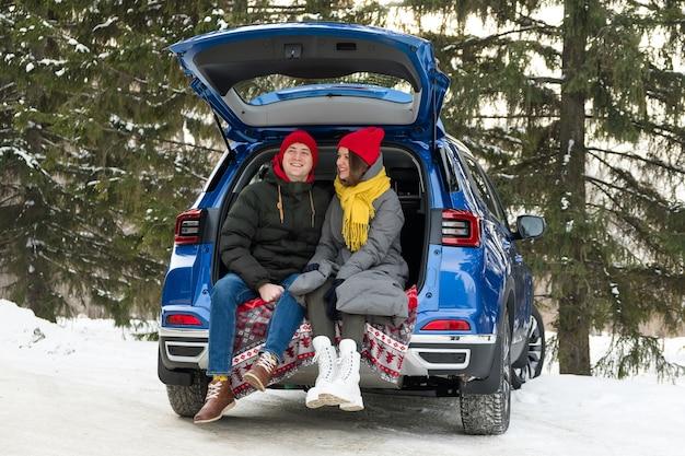 Coppie romantiche giovani hipster che abbracciano mentre sedendosi nel bagagliaio dell'auto. amore, celebrazione del giorno di san valentino