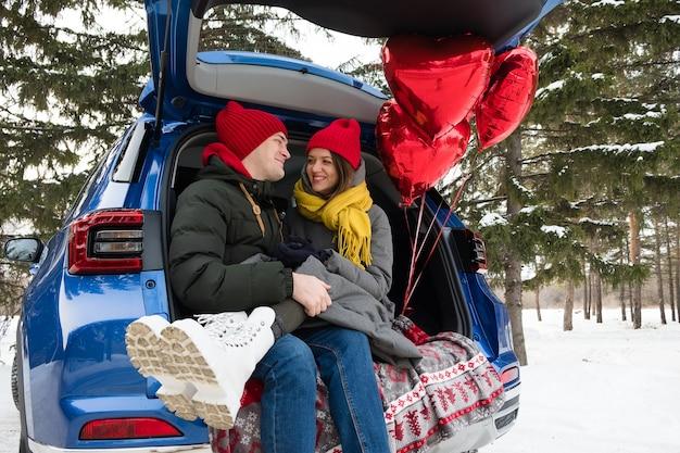 Coppie romantiche giovani hipster che abbracciano mentre sedendosi nel bagagliaio dell'auto. amore, san valentino