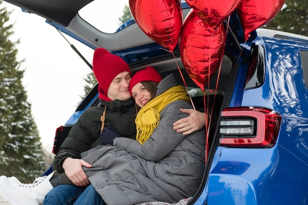 Coppie romantiche giovani hipster che abbracciano mentre sedendosi nel bagagliaio dell'auto