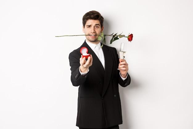 Romantico giovane in abito che fa una proposta, tenendo la rosa tra i denti e un bicchiere di champagne, mostrando l'anello di fidanzamento, chiedendo di sposarlo, in piedi su sfondo bianco.