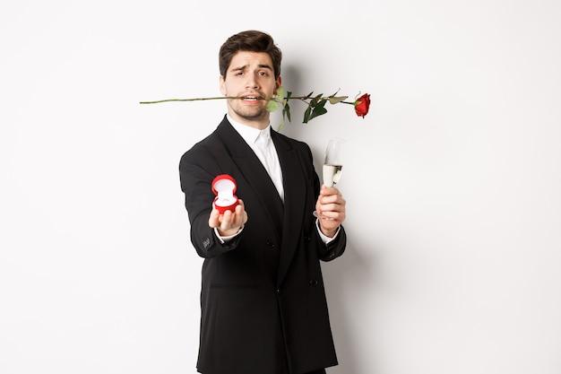Giovane romantico in abito che fa una proposta, tenendo la rosa tra i denti e un bicchiere di champagne, mostrando l'anello di fidanzamento, chiedendo di sposarlo, in piedi su sfondo bianco