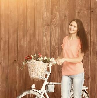 Una giovane donna romantica che guarda la telecamera con la sua bici e un cesto di fiori di campo estate