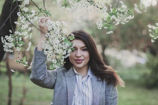 Giovane donna romantica nel giardino primaverile tra la fioritura dei meli.