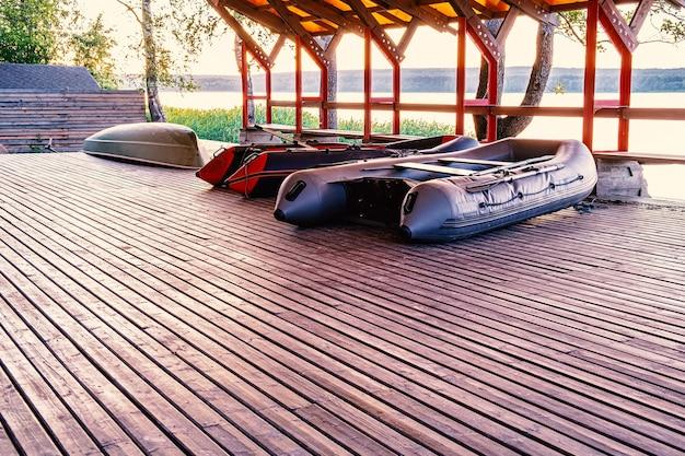 Sotto il tetto ci sono due barche da pesca gonfiabili e una barca da diporto in plastica stendibiancheria in un villaggio di pescatori