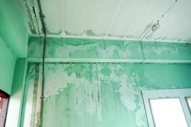 Tetto del soffitto danneggiato dall'acqua di perdita del tetto e macchia sul primo piano del soffitto