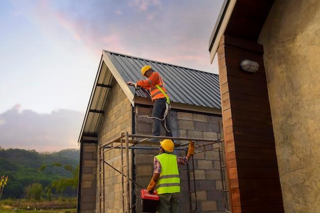 Roofer operaio edile installa nuovo tetto, utensili per coperture, trapano elettrico utilizzato su nuovi tetti con lamiera.